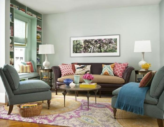 muebles de salon, salón pequeño con sillones azules con patas de madera, sofá con cojines, mesa redonda, estantería alrededor de ventana