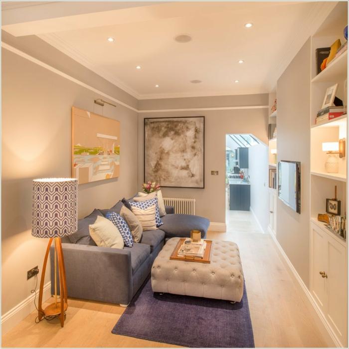 muebles de salon, salón estrecho con sofá azul y cojines, mesa taburete, tapete púrpura, suelo laminado y dos cuadros