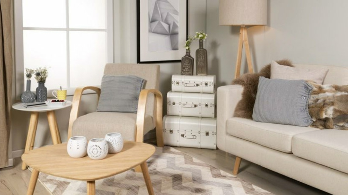 muebles de salon, salón pequeño con sillón y sofá beige, mesa de madera, decoración con maletas vintage y flores en botellas