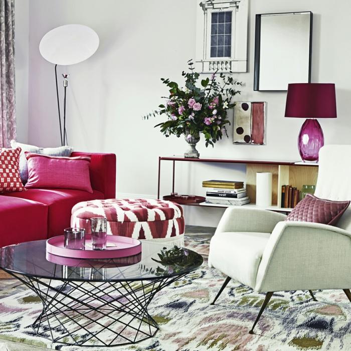 muebles de salon, salón pequeño con mesa redonda de vidrio, sofá ciclamen, espejo de pared y flores