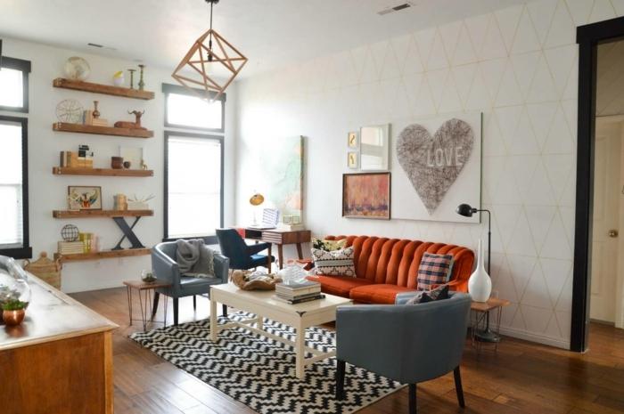 muebles de salon, salón pequeño con sofá naranja y dos sillones azules, mesa rectangular blanca, estantería con decoraciones y cuadro con corazón