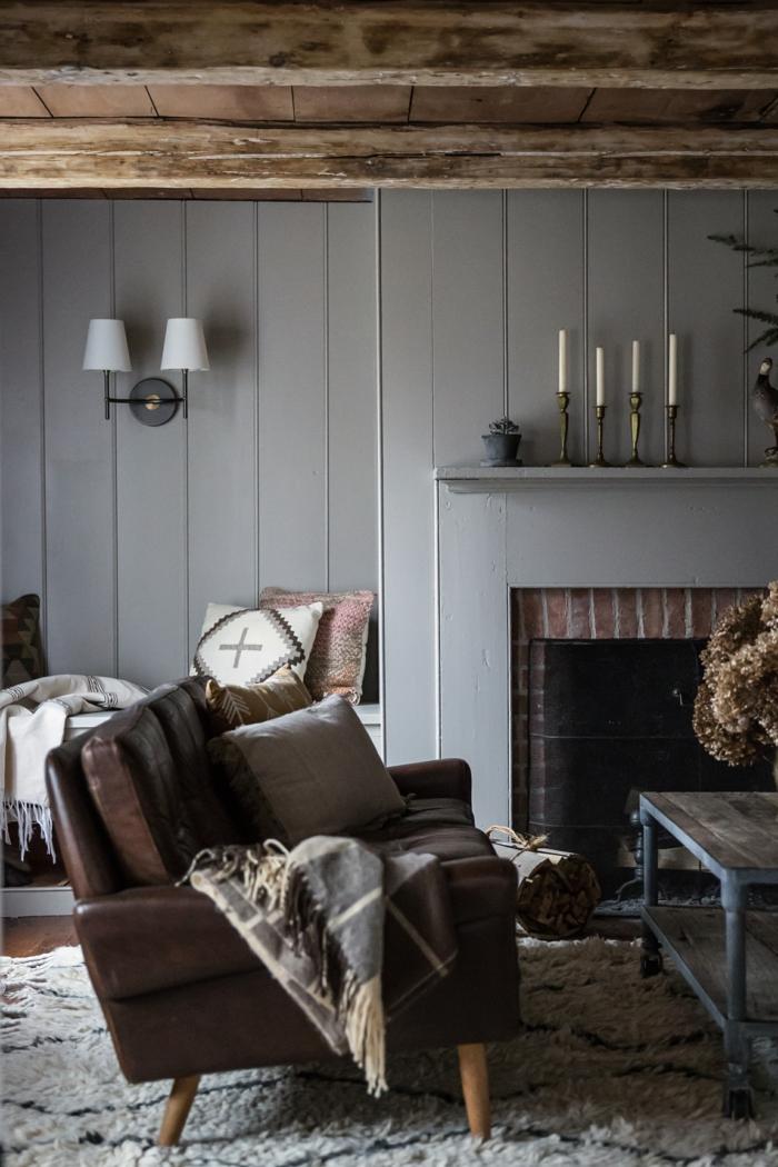 muebles salon, pared de madera con chimenea, sofá tapizada piel, cojín y cubierta, candelas