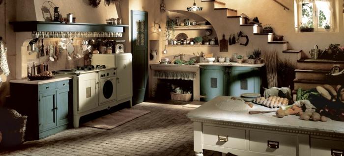 cocina rustica, cocina con isla y poca luz, suelo de baldosas, alacenas en blanco y azul., escaleras bajo ventana