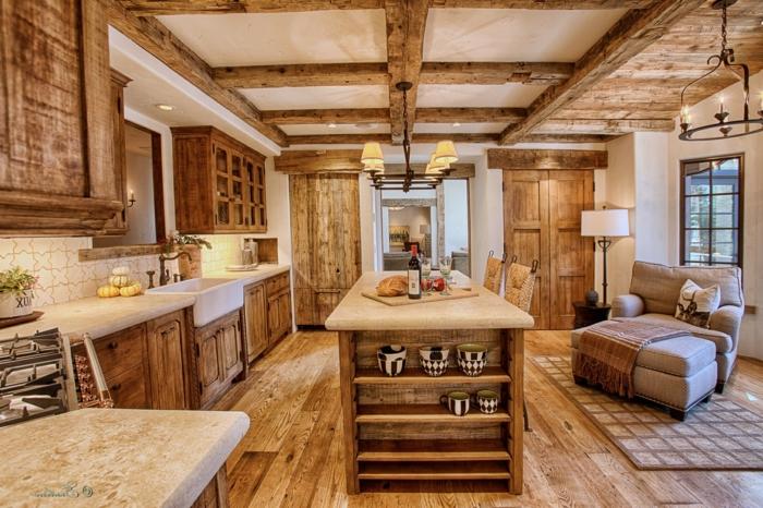 cocina rustica, cocina grande con paredes y techo de madera, isla rectangular con sillas, tapete y sillón