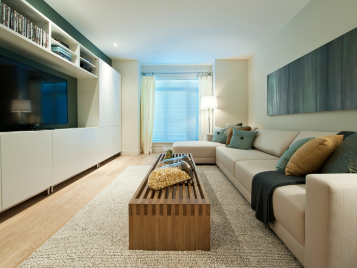 salones pequeños, salón estrecho con sofá beige en forma de L, mesa de madera, cojines azules, estantería y televisor