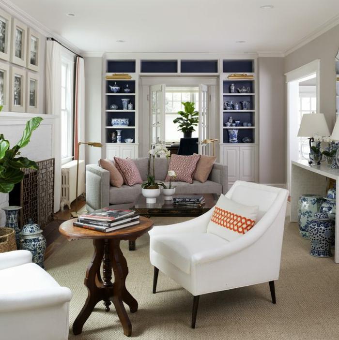 salones pequeños, salón con mesa redonda y sillón blanco. sofá con cojines. estantería blanca con jarras de porcelana