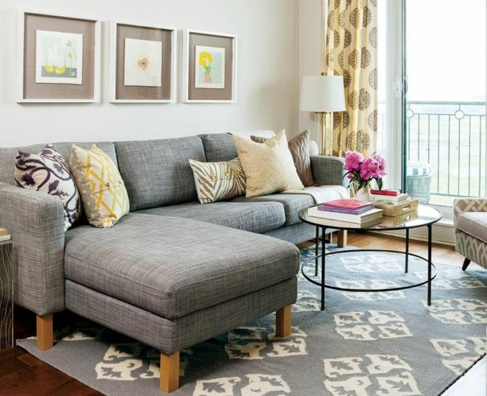 salones pequeños, salón con sofá gris en forma de L, tres cuadros, ventanal y mesa redonda de vidrio con flores