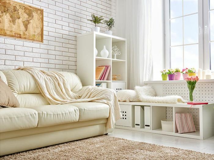 sslon, espacio pequeño con ventana grande, sofá de piel beige, pared de ladrillo blanco con mapa del mundo, estantería blanca con flores