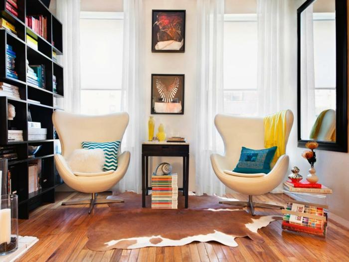 salones pequeños, salón simétrico con dos sillones iguales, cojines azules, librería negra y alfombra piel de vaca