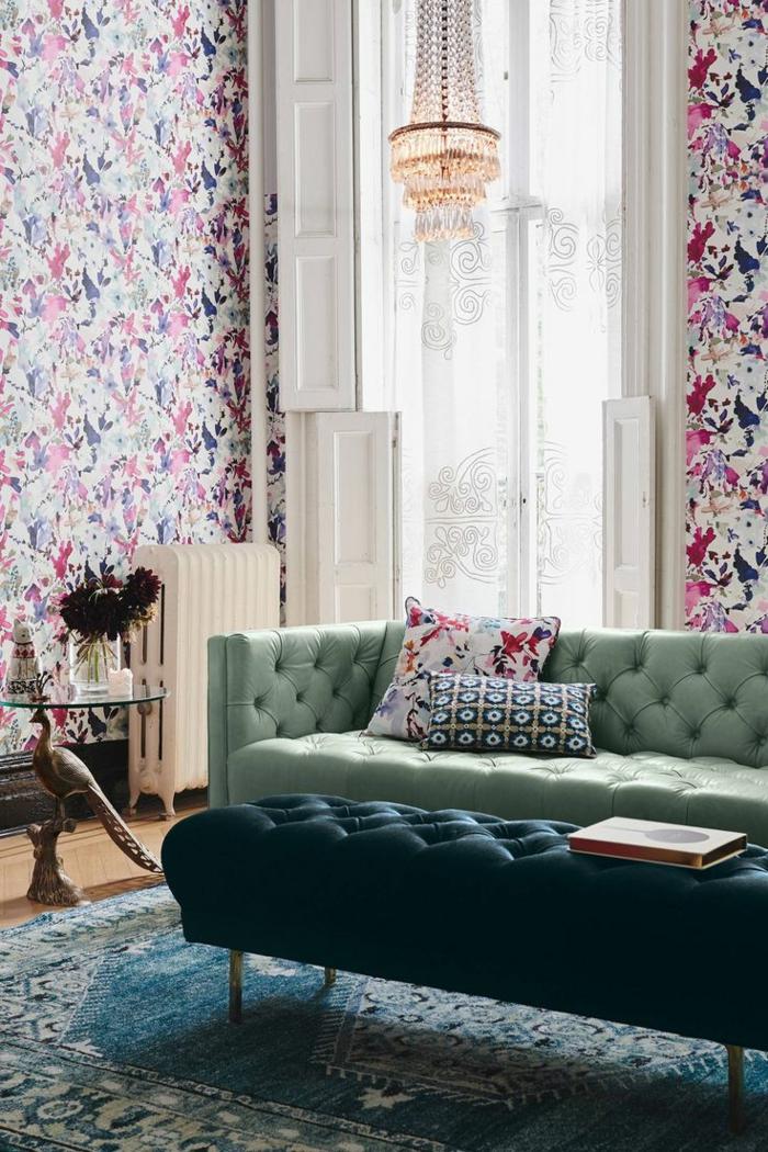 salon, espacio pequeño con papel pintado rosado, techo alto y ventanal, lámpara de araña, sofá y taburete largo