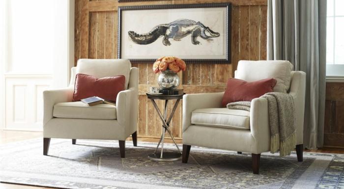 decoracion de interiores salones, salón con dos sillones iguales, cojines rojas, pared de madera y cuadro con cocodrilo