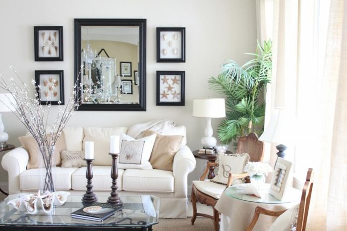 salones modernos, salón con espejo grande, sofá blanca con cojines beige, mesa de vidrio con candelas y flores, dos sillas, planta verde