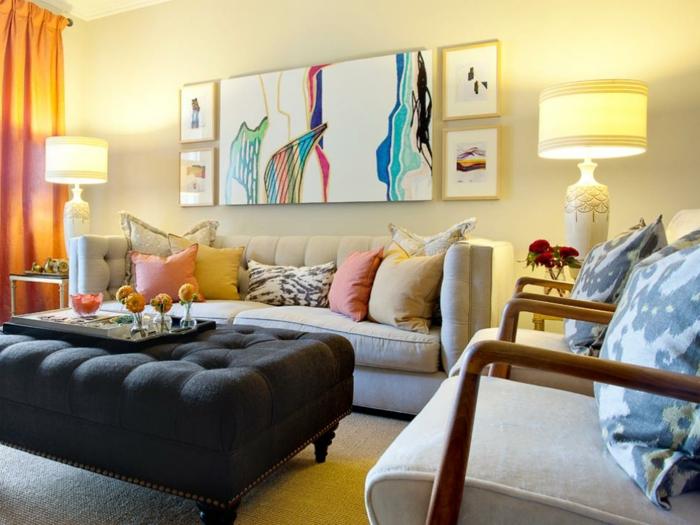 salones modernos, salón con cuadro abstracto, sofá beige con cojines, sillones y taburete de mesa, lámparas simétricas