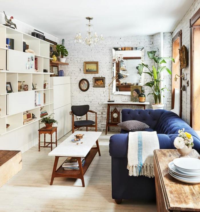 decoracion salones pequeños, salón con estantería blanca y sofá azul, pared de ladrillo y lámpara de araña, mucha luz natural, plantas verdes