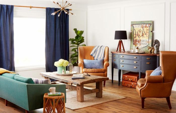 muebles de salon, salón pequeño vintage, sillones de piel, mesa de madera desgastada, sortinas azules, sofá verde y tapete