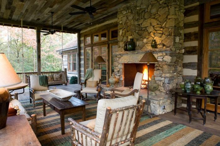decoracion salones, chimenea rustica de piedra, mesa de madera, sillones, tapete y ventanales