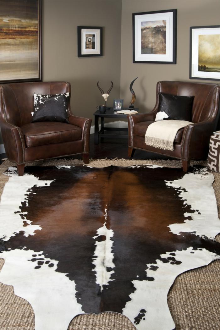 decoracion salones, piel de vaca, sillones de piel con cojines negros, mesita y cuadros
