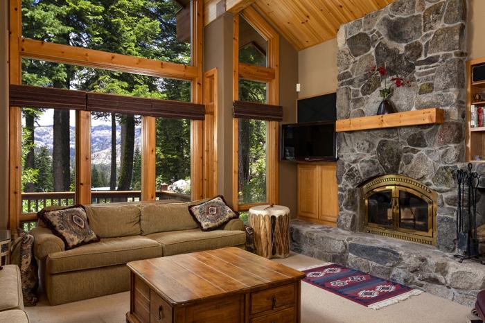 decoracion salones, salon rustico, chimenea de piedra, ventanales, sofá con cojines y mesa de madera