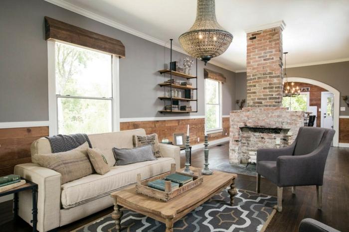 decoracion salones, salon rustico, chimenea de ladrillo, sofa beige con cojines, mesa con libros y portavelas