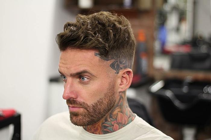 cortes de pelo cara redonda, undercut militar con rizos, laterales rapados, barba corta, hombre con tatuajes