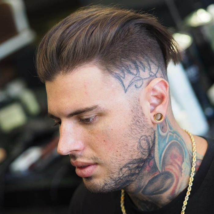 tendencias pelo 2018, pelo castaño, larga franja hacia atrás, laterales rapados con tatuajes, flash en la oreja