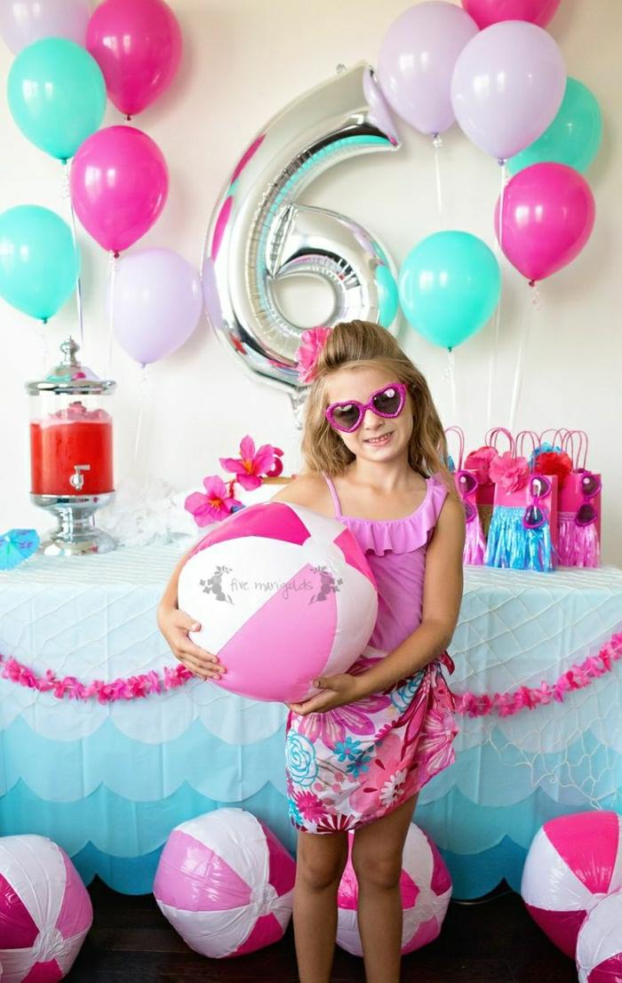 decoracion con globos, niña con gafas de sol rosa, globos azul y rosado, mesa con regalos