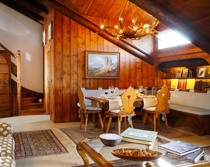 mueble salon, decoracion rustica con paredes y techo de madera, lámpara con cuernos, sillas y escalera