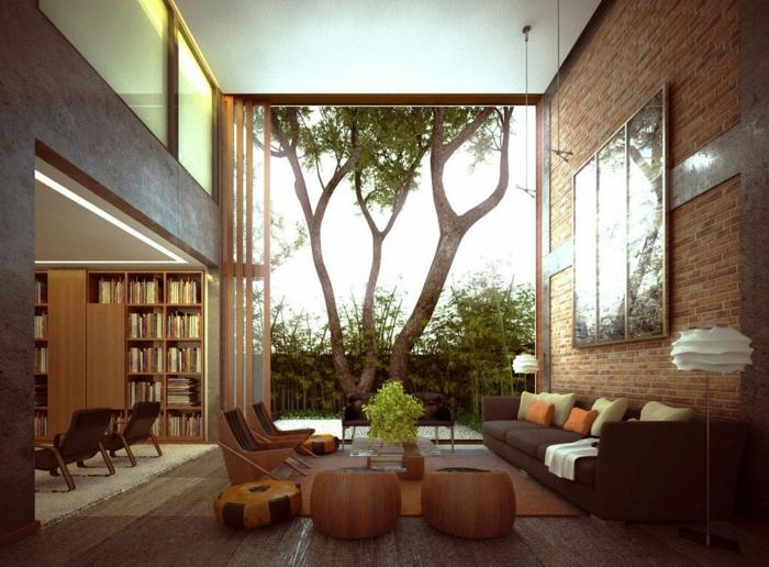 mueble salon, ventanal con arbol, pared de ladrillo con cuadro, librería, sofa, turcas y sillas