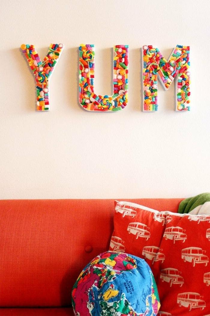 manualidades faciles, decoración para pared con letras hechas de dulces, sofá y cojines