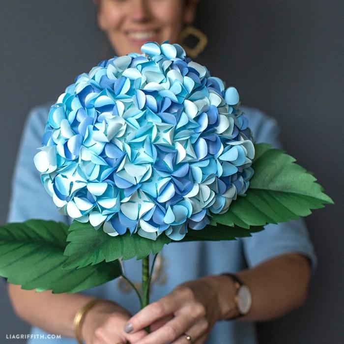 flores de papel, mujer con reloj y glor grande de papel en tonos azules con hojas verdes