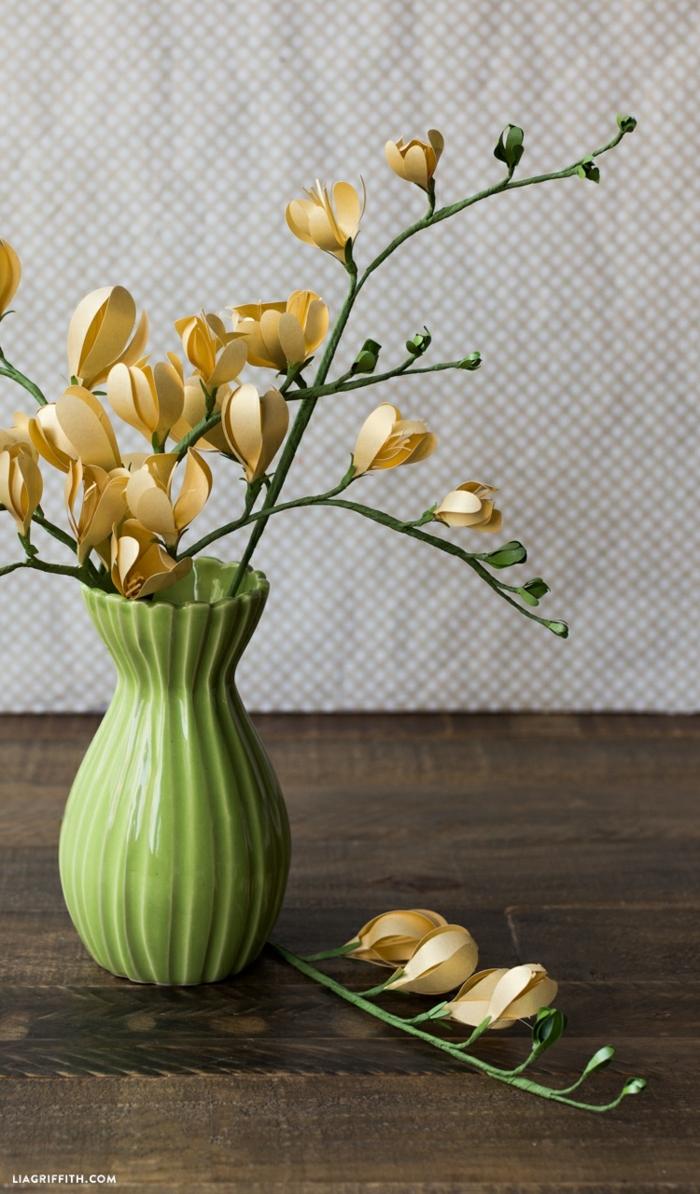 plantillas de flores, fresia de papel en jarra verde sobre mesa de madera