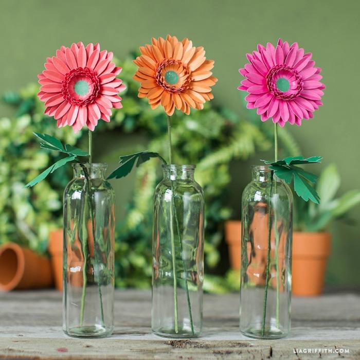 flores de papel, gerberas en rosado y naranja hecho de papel en botellas de vidrio