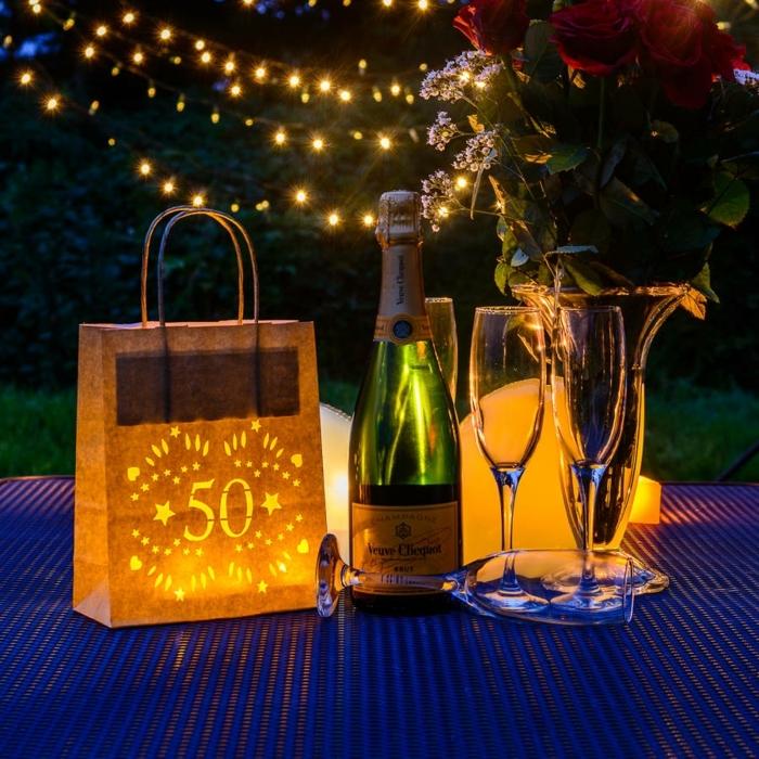 decoracion cumpleaños, notella de champaña con vasos, bolsa de regalo con edad iluminada