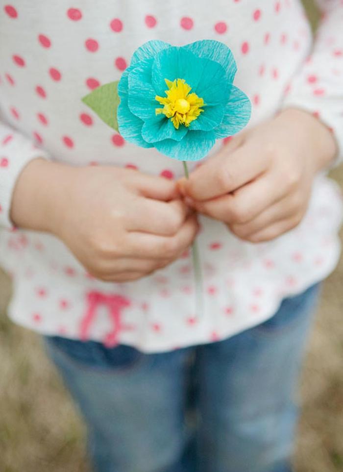 como hacer una rosa de papel, niño con una flor azul de papel pinocho en las manos
