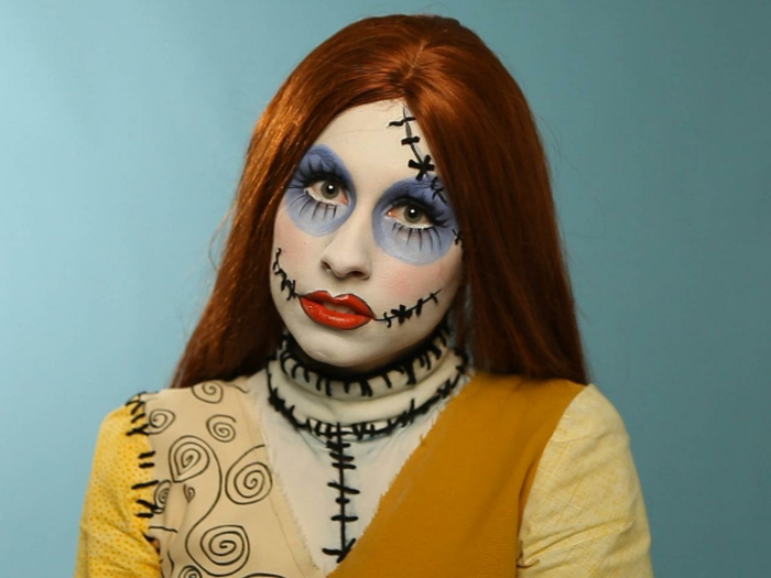 maquillaje vampiresa, mujer pelirroja maquillada para halloween, ojos en purpura, labios rojos, pies cosida