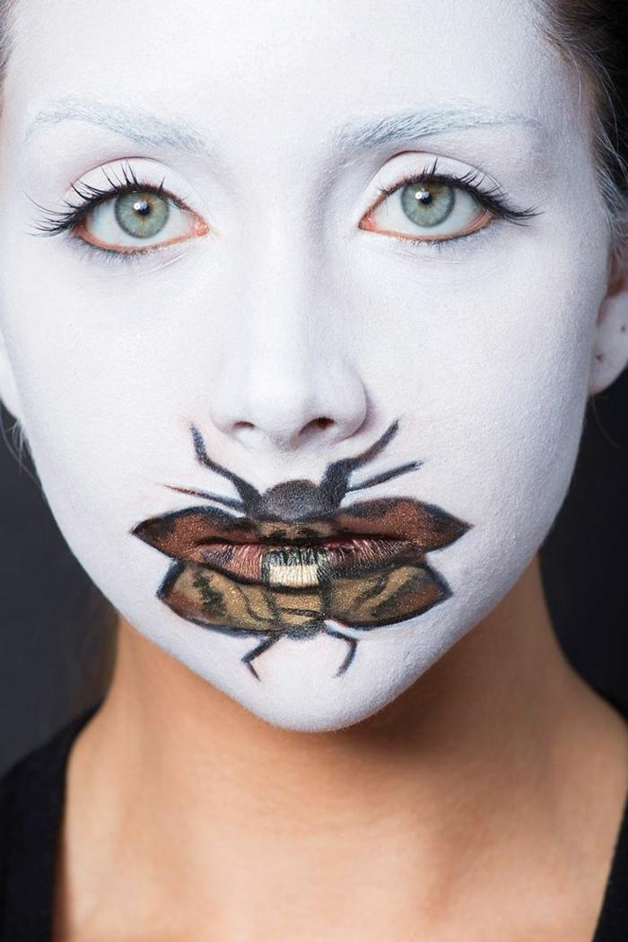 maquillaje halloween, mujer maquillada con cara en blanco y mosca pintada sobre los labios