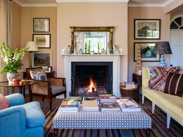 ideas decoracion, espejo sobre chimenea, mesa con libros, pared cuadros, sillones y sofá