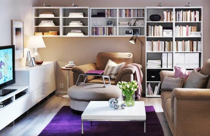 decoracion de salones, salón pequeño con sofá y sillón, estantería con libros, mesa cuadrada blanca con flores, tapete lilá