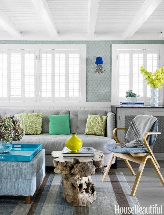 decoracion de salones, salón con persianas blancas, sofá gris con cojines, mesa rústica, tapete y silla de madera