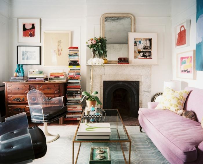 decoracion de salones, salón peque;o con chimenea y sofá lilá, sillas vintage negras, mesa rectangular de vidrio