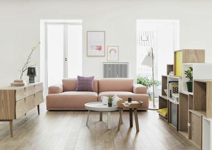 decoracion de salones, salón estilo escandinacvo con sofá en rosado, ventanales, mesas de café redondas y estanterías bajas