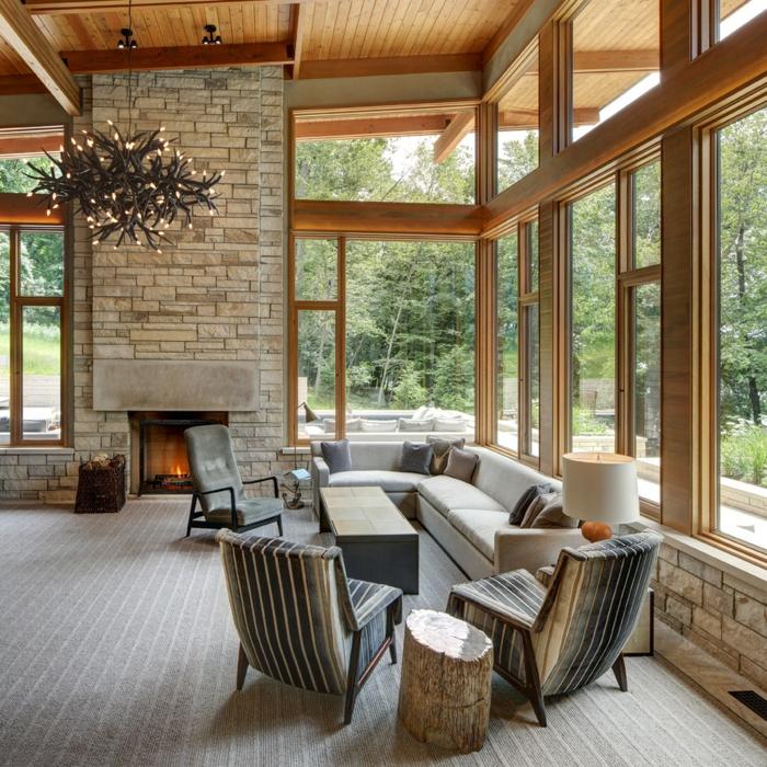 decoracion de salones, chimenea de piedra, ventanales grandes, mesa con sillas y sofá, lámpara de araña