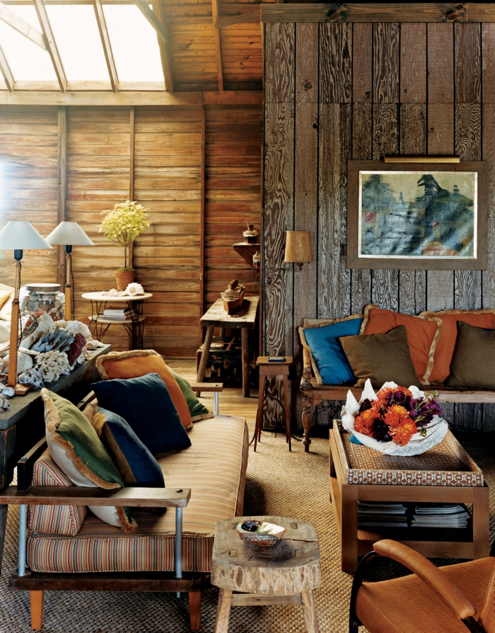 decoracion de salones, sofá con cojines multicolor, paredes de madera, mesa con flores, cuadro