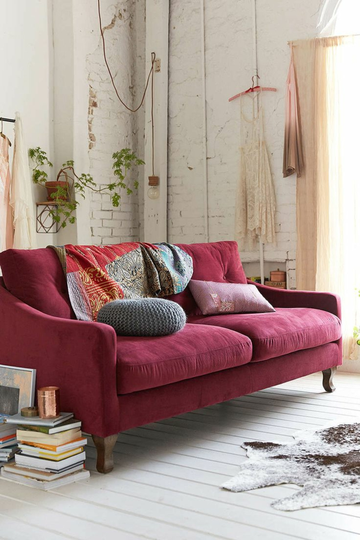 salones modernos, salón estilo industrial con pared de ladrillo y techo alto, sofá color ciclamen, suelo de tarima blanca, percha con vestido colgante