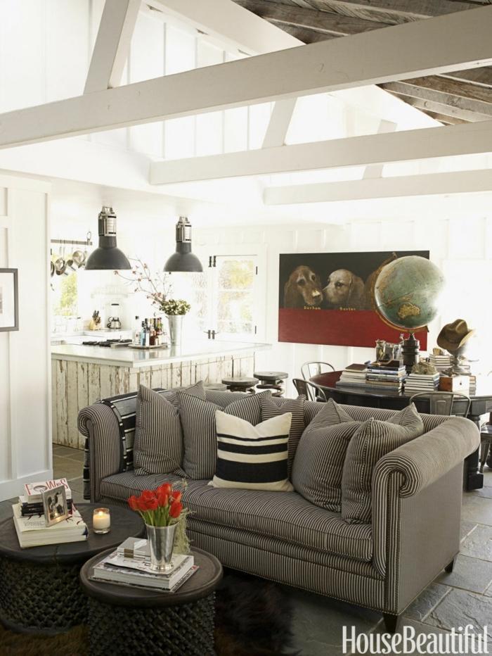 salones modernos, salón pequeño con sofá en blanco y negro, lámparas colgantes, cuadro con perros y globo, techo con vigas