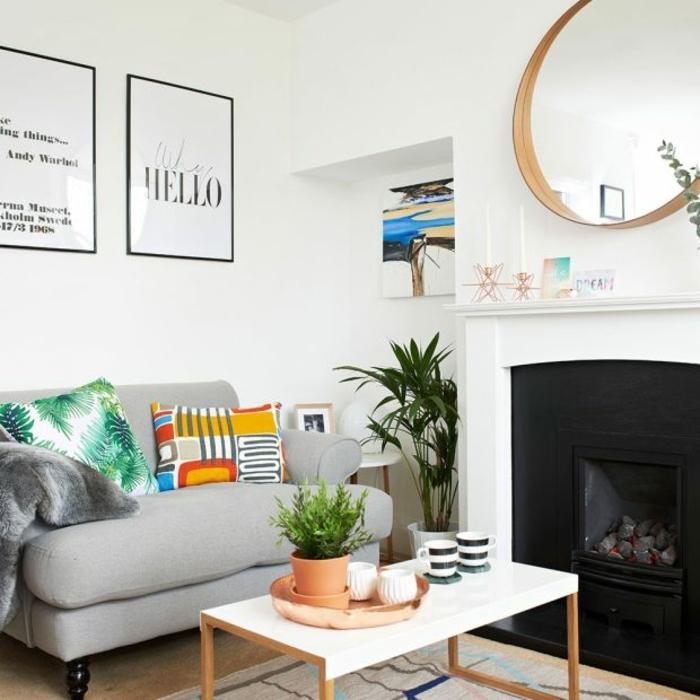 salones modernos, salón pequeño con sofá gris, mesa de madera blanca y chimenea de metal, espejo redondo