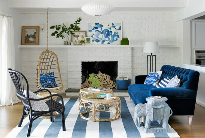 decoracion de interiores salones, salón pequeño en azul y blanco con chimenea, sofá y columpio, techo bajo y mesas tejidas