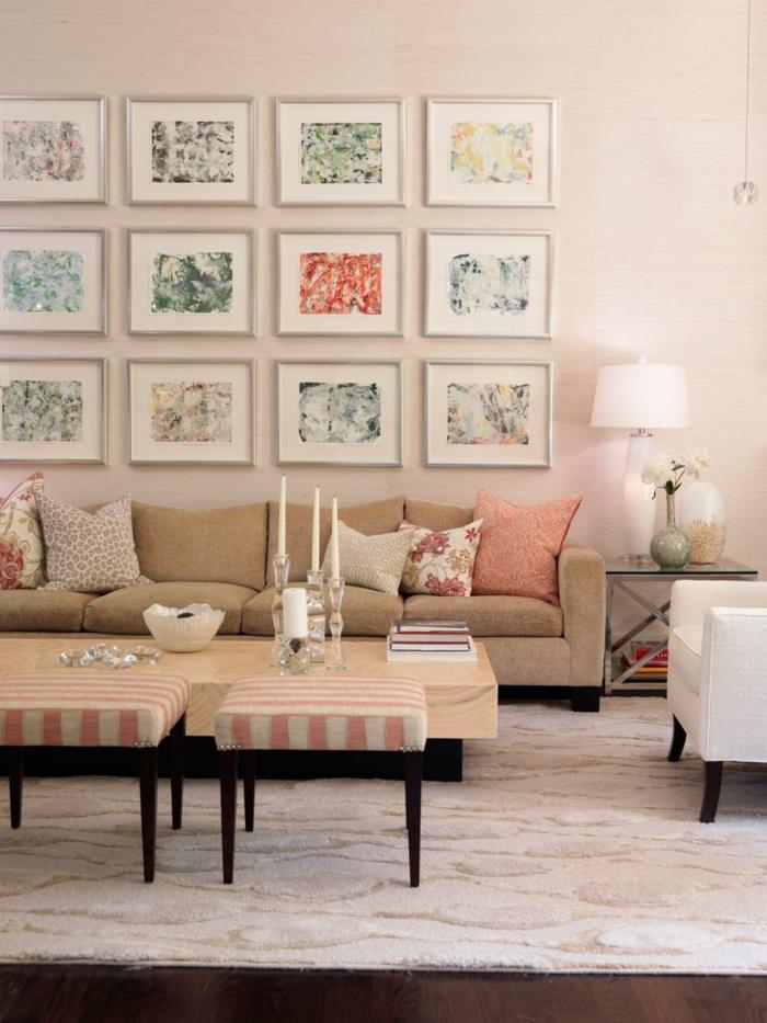 decoracion de interiores salones, salón con mesa de madera y portavelas, sofá beige con cojines rosados, muchos cuadros con motivos florales
