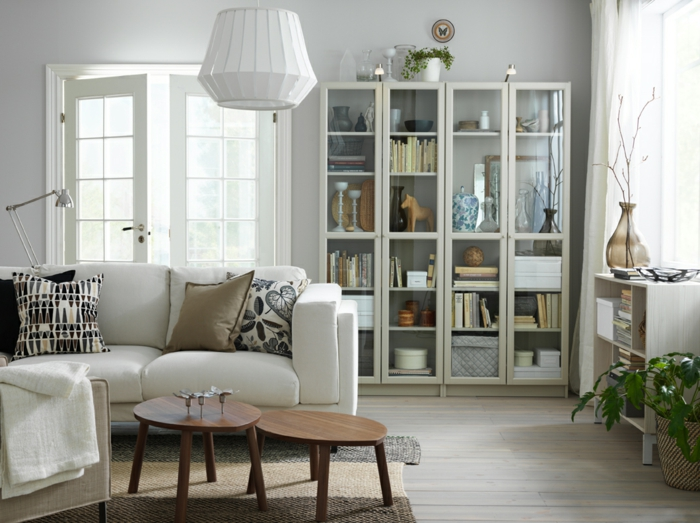decoracion de interiores salones, salón con sofá blanco con cojines, ventana puerta, estantería con puertas de vidrio, mesas de madera
