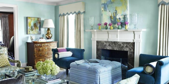 decoracion de interiores salones, salón en tonos azules con chimenea, mesa de vidrio con flores, cortinas beige y cuadro